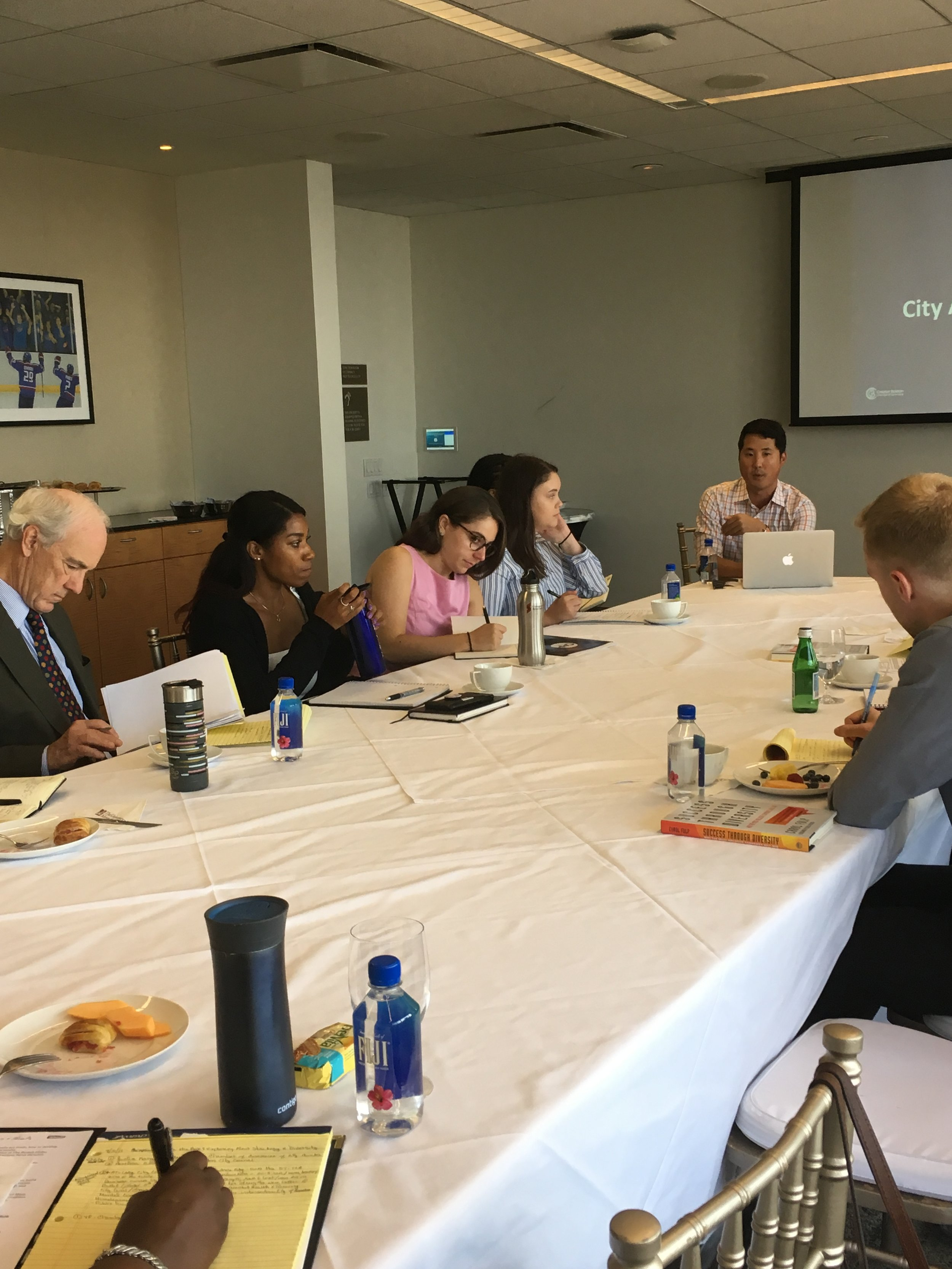 Robert Turner, Director of Pinnacle Projects, and Jessica Amedee, Liz Berman, and Sarah Nordberg, listen to Justin Kang  VP of the Greater Boston Chamber of Commerce and Founder of City Awake at the UMass Club on 7.31.