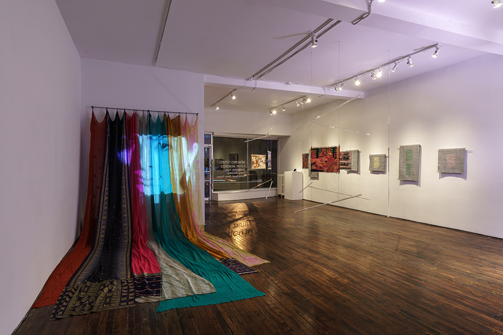 Veena  (2016) is an installation in Saris are hung from the ceiling cascading onto the floor. A video portrait is then projected onto the extended fabric which pans in and out of a young woman, focusing on specific aspects of her body. The accompanying audio recounts the story of Veena, a narrative of an Indian woman sharing her experience of migrating to England many years ago. The voice of Veena comes from the Apple dictation accents from Apple inc.   This installation aims to play with the viewer's perception of authenticity and narrative. Visually the viewer is confronted with a feminine display of delicate patterned fabric and the visualization of a woman. Coupled with the audio, it is unclear if the voice of Veena is in fact a real human, a computer, or someone for whom English is a second language. This fluxes is meant to point to ideas of false nostalgia, orientalism and exotisicm that is often found in works from artists who come from diasporic communities.