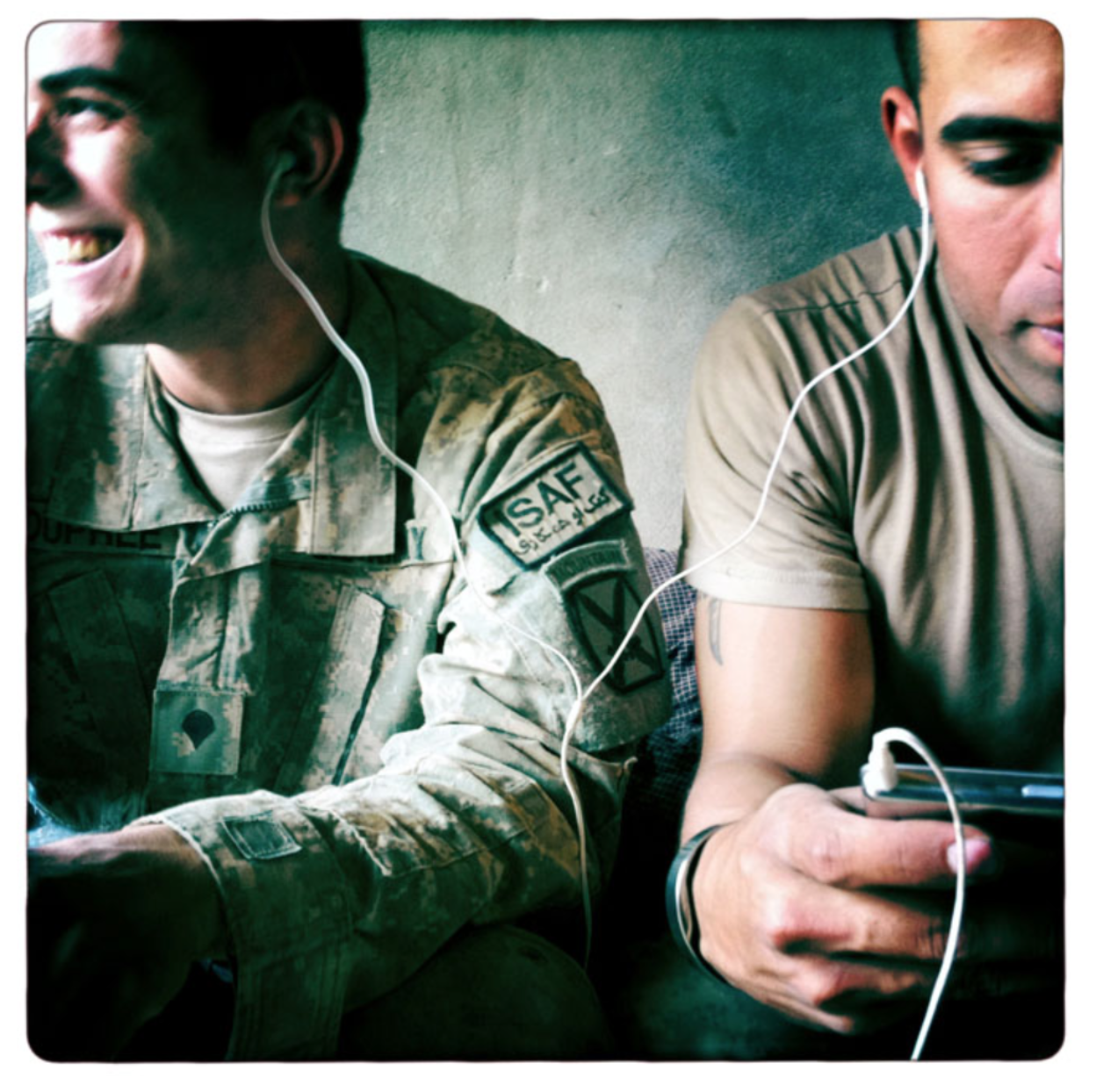 Figure 1: Damon Winter, 'Specialist Christian Dupree and SGT. Santiago Zapata Sharing Earbuds To Listen To Music' from A Grunts Life,