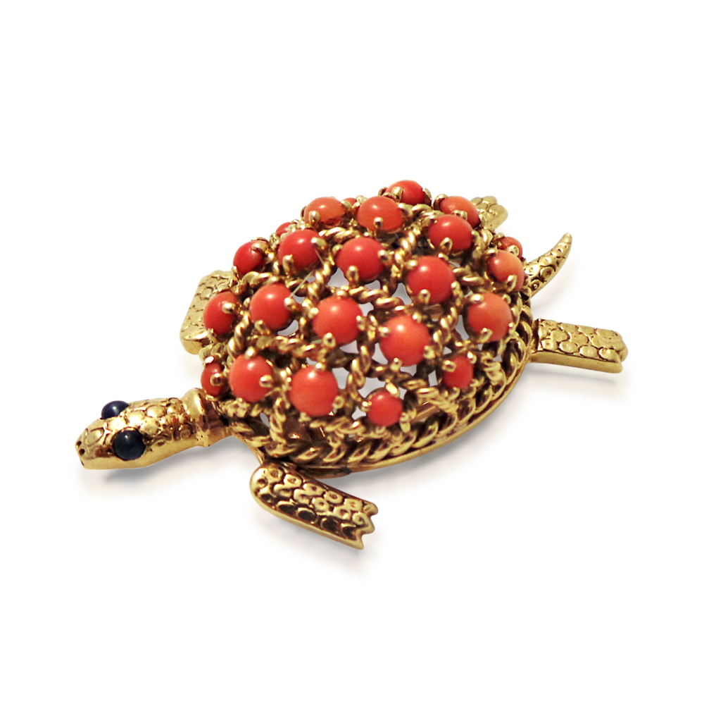 A coral and gold turtle brooch by Cartier for the man who dresses to impress. Shell set with Mediterranean red coral cabochons, with ropetwist details, enhanced by sapphire cabochon eyes, mounted in platinum and 18k yellow gold. With French assay marks, maker's mark, signed 'Cartier Paris' and numbered '128729', circa 1950.