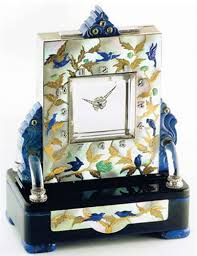 """This """"Mystery clock"""" was made in 1931 and exhibited at the 1939 World Fair. Designed by Vladimir Makovsky and made by Pierre Gravoin, it consists of platinum, 18k yellow gold, mother-of-pearl, lapis lazuli, turquoise, rock crystal, black onyx, diamond-set and emerald-set, with winding/setting key. By Vladimir Makovsky for Black, Starr & Frost."""