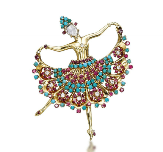 A multi-gem ballerina brooch, by John Rubel  Designed as a dancer set with an inverted rose-cut diamond face, holding the edges of her skirt set with rubies, diamonds and cabochon turquoises, mounted in gold,  circa 1945, 7.0 cm.  Signed John Rubel Co.   Image Courtesy of Christie's.