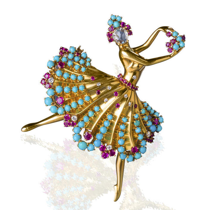 """A diamond, ruby, and turquoise """"Clip Danseuse"""" brooch, Van Cleef & Arpels, 1943. Designed as a ballerina with pear-shaped rose-cut diamond face, her tiara, skirt and bouquet accentuated by circular-cut rubies, old European and single-cut diamonds, and cabochon turquoise;  signed Van Cleef & Arpels, N.Y. no. 4157; mounted in eighteen karat gold; length: 2 3/4in.    Image courtesy of Bonhams."""