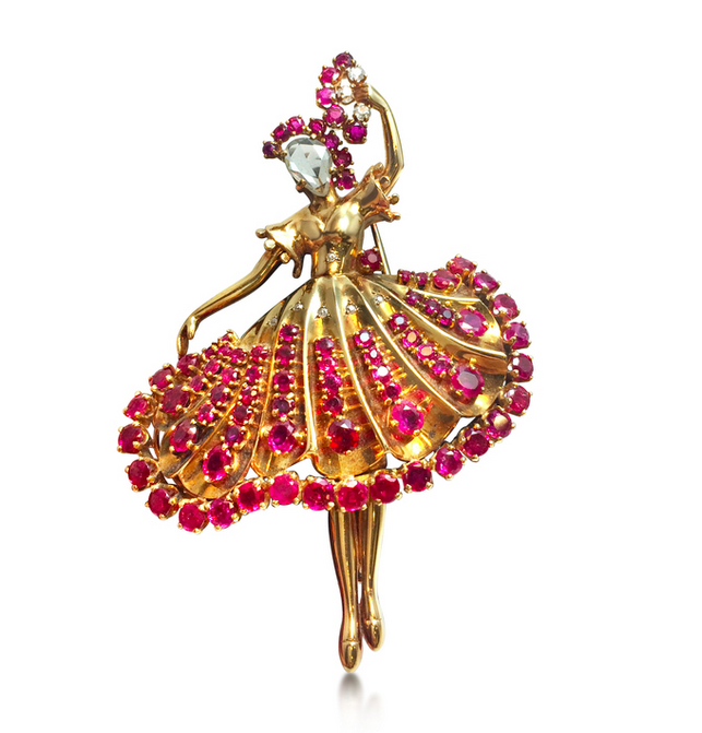 A ruby and diamond ballerina brooch, attributed to John Rubel. Designed as a dancer set with an inverted rose-cut diamond face, holding the a fan set with rubies and diamonds, mounted in gold,  circa 1945, 7.0 cm.