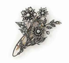 A late 19th century diamond brooch and pin with two diamond cluster flower-heads set en tremblant, mounted in silver and gold, circa 1890. Up for auction at Christie's this April, it features old circular-, rose-, and single-cut diamonds.