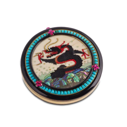 A Gem-Set Compact, by Cartier, 1920s    The circular compact with a water dragon motif composed of resin, ivory and mother-of-pearl, framed by black enamel, turquoise, and cabochon rubies, opening to reveal a powder compartment and a mirror, measuring approximately 65mm x 65 mm x 12mm, signed Cartier London, New York, Paris and numbered, French assay marks.    Photo courtesy of Symbolic and Chase.