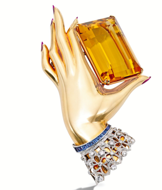 Flato was especially attracted to hand imagery, which was a frequent theme in his pieces.   A Gold, Platinum, Citrine, Ruby, Diamond and Sapphire Clip-Brooch, by Paul Flato The polished gold hand with five drop-shaped cabochon ruby fingernails holding an emerald-cut citrine weighing approximately 100.00 carats, the lace cuff set with round and single-cut diamonds weighing approximately .50 carat, accented by 15 calibré-cut sapphires; circa 1940.