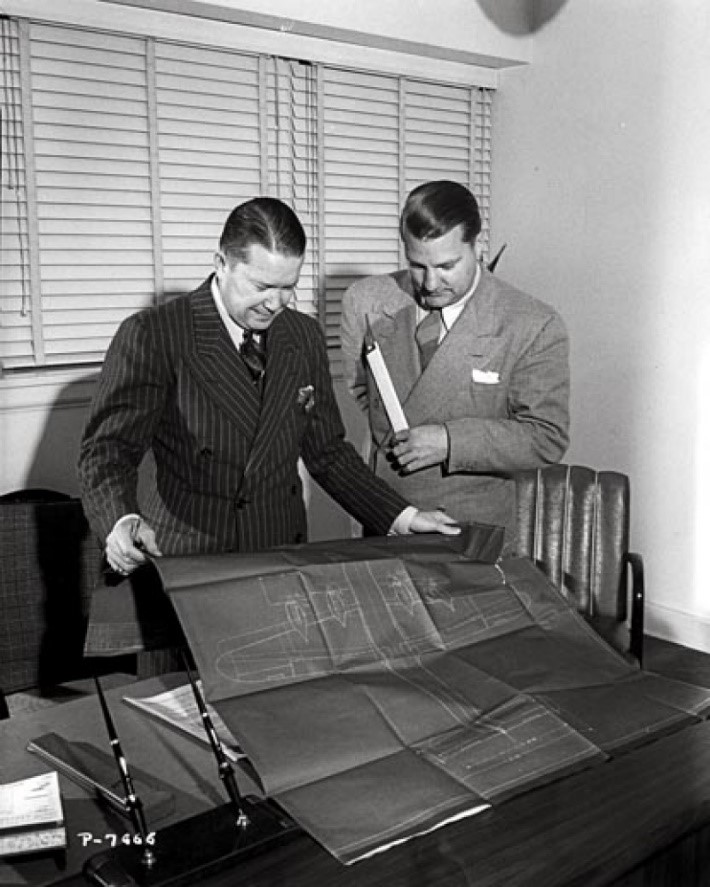 """Hall Hibbard (left) and Clarence """"Kelly"""" Leanord Johnson (1910-1990) holding a K&E or Dietzgen slide rule. Both looking at a blueprint of the the Lockheed Constellation. Kelly Johnson was the engineer on 42 of the most famous planes in aviation history, including the P-38 Lightning, Constellation, the U2 and the SR71), which all were designed using slide rules."""