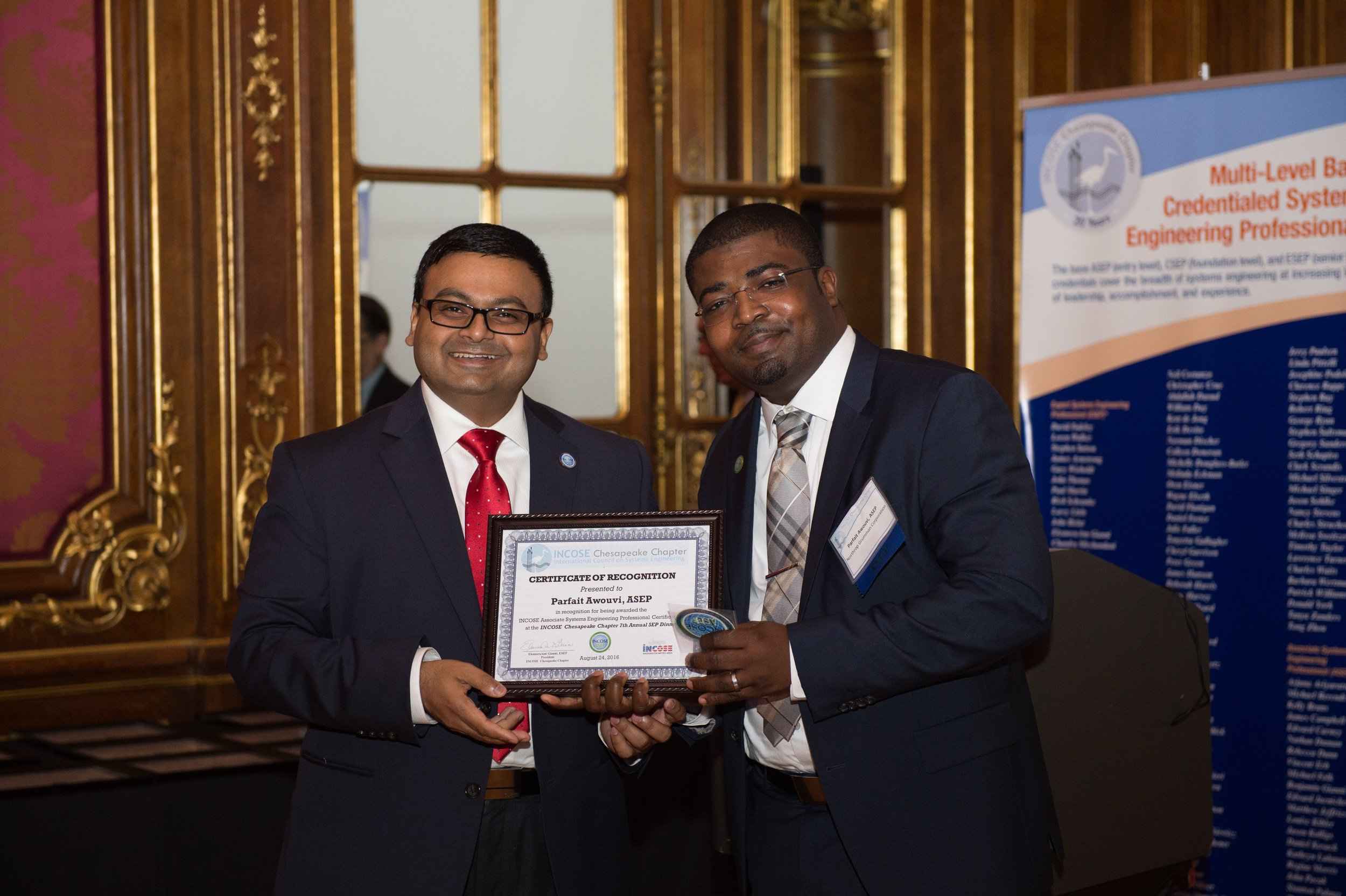 Dr. Muhamad Islam, CSEP, President of WMA, presents an ASEP Certificate of Recognition to Mr. Parfait Awouvi from Northrop Grumman Corporation.