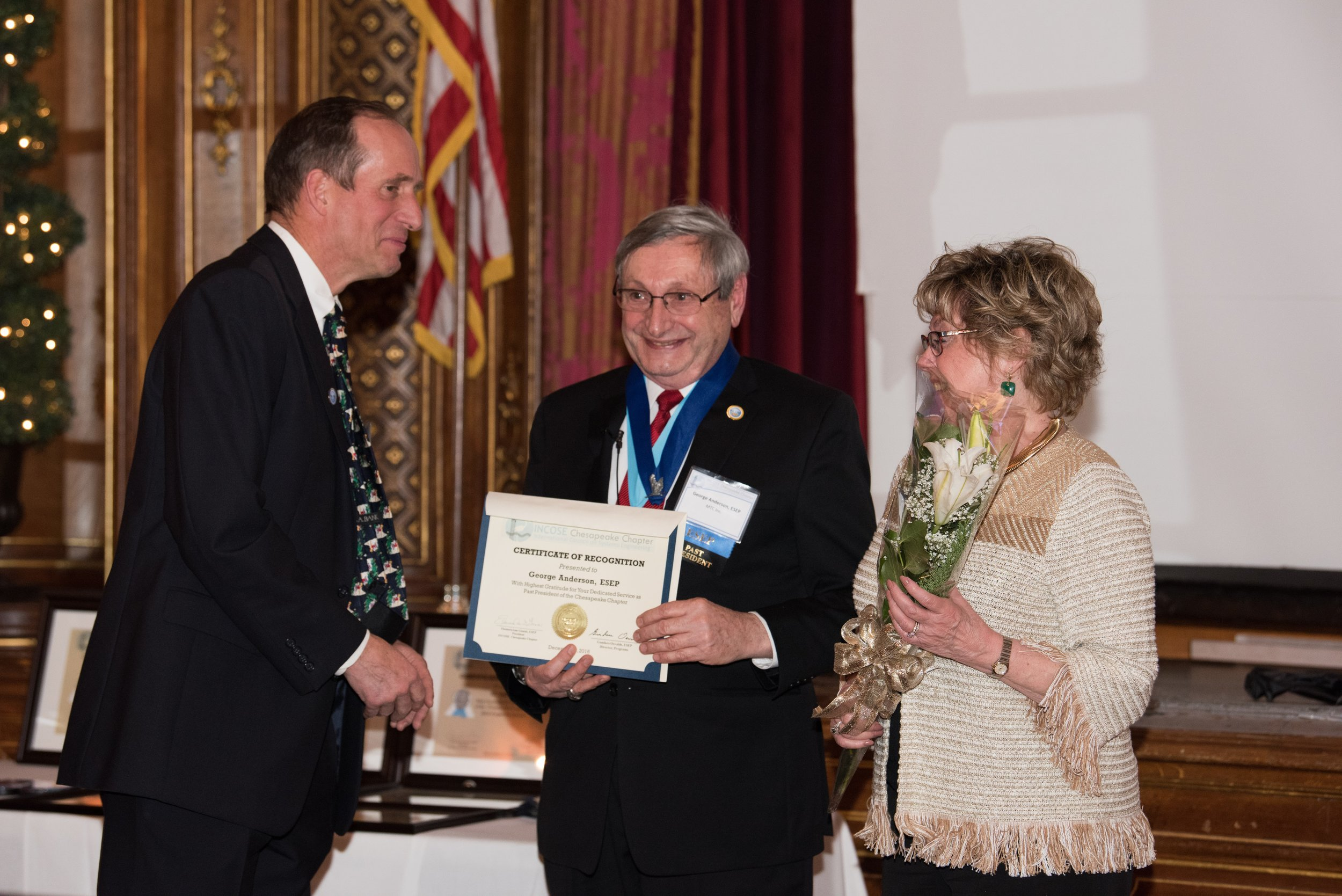 "Mr. George W. Anderson, ESEP, receives the Past President's Award for his service to the INCOSE Chesapeake Chapter. Mrs. Doreen Anderson also is recognized with a presentation of flowers from chapter Communications Director, Pat Williams, CSEP, for her, ""Years of Service"", as the spouse of a Chesapeake Chapter President."