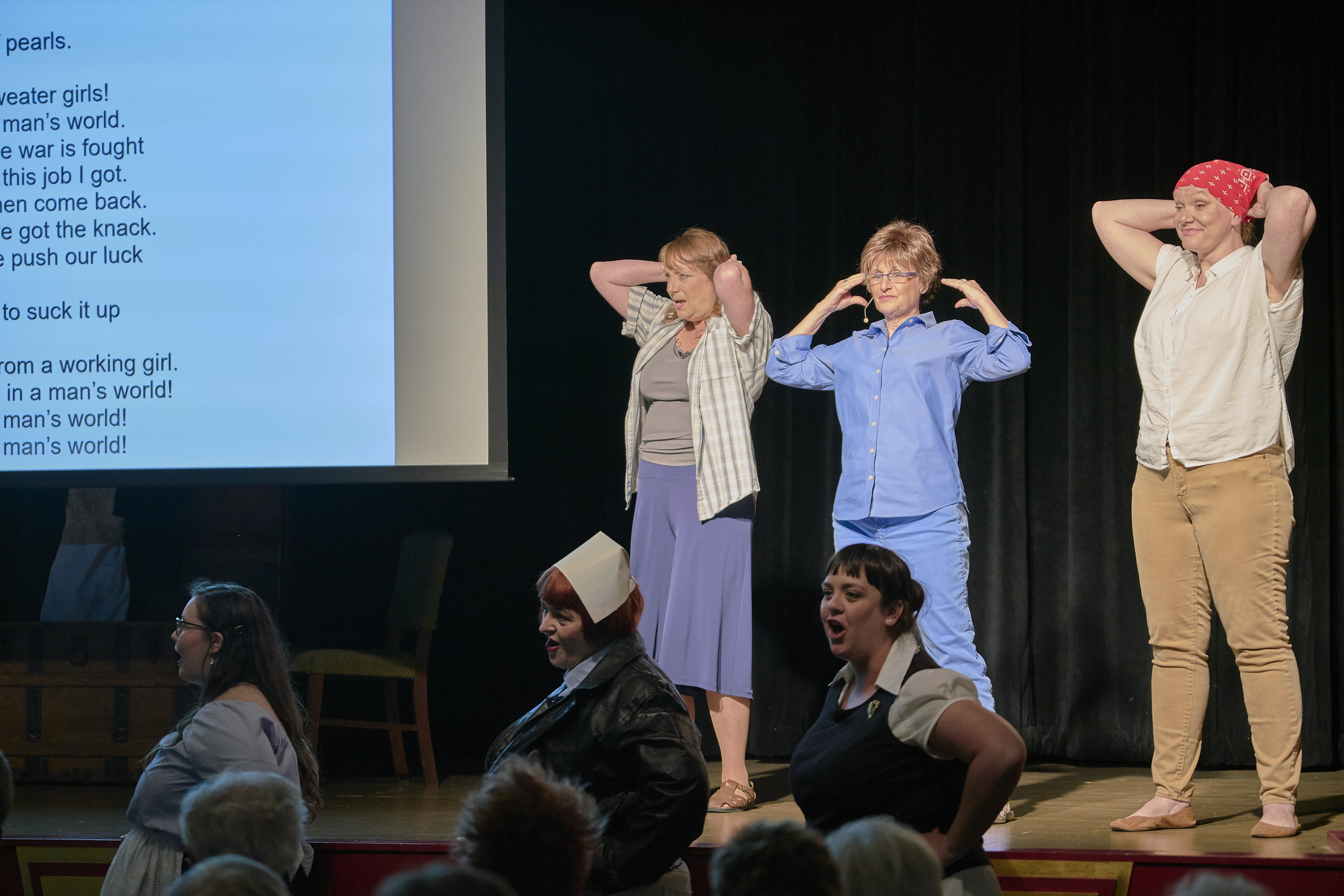 "L to R on stage, Lisa Green as Dorothea Lange, Darla Hoffmann as Narrator, and Liz Vincent as Adeline Van Buren; and L to R below stage, Brooke Sauter as Hazel Funk Holmes, Stephanie Rhein as Edna, a Phillips 66 Highway Hostess, and Karen Wright as Ray Eames sing ""Bandanas tied around our curls"" in the original song, ""Making Good in a Man's World,"" the finale to Act One in the Pontiac production June 22-23. (Photo by Mitchell T. Fransen, courtesy of the City of Pontiac.)"