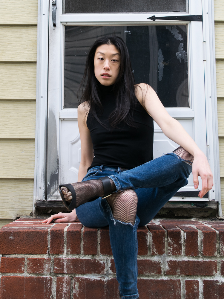 Female in cute Summer Outfit with Blue Jeans, Fishnet stockings, and black crop top