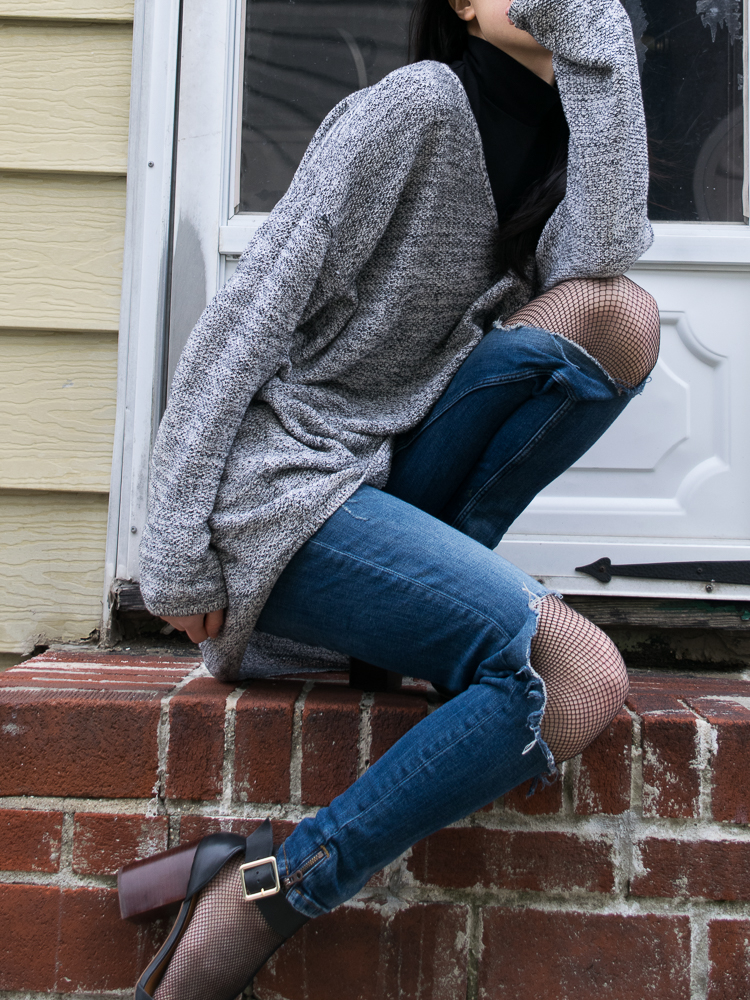 Close-up shot of cute summer outfit - layered sweater, Blue Jeans and Fishnet Tights
