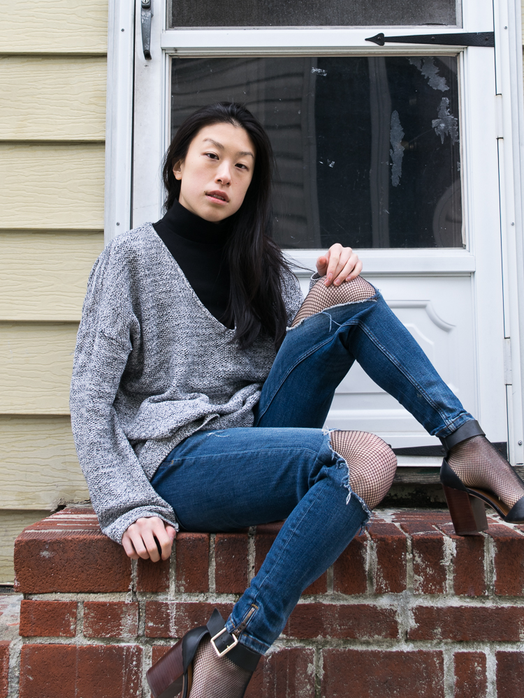 Female blogger in ripped blue jeans, black heeled steve madden sandals, black cropped turtle neck, heather sweater