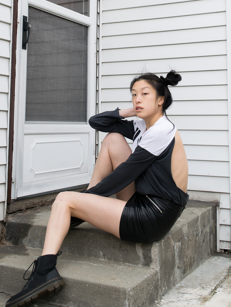 Female east asian blogger in longsleeved athleisure backless top, pleather skirt, black canvas doc martens boots, sitting on stoop