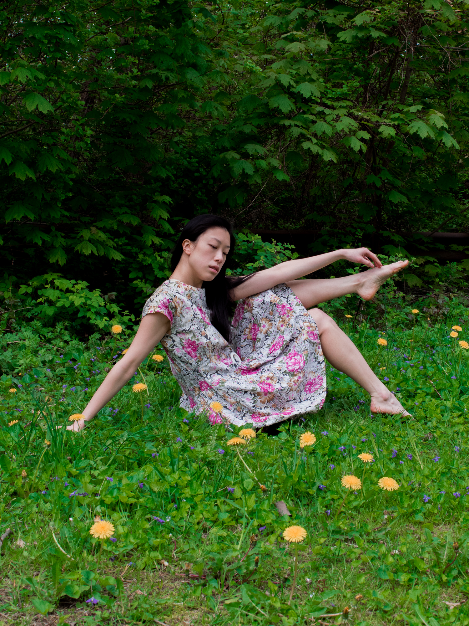 Taiwanese blogger in vintage pink floral dress sitting in meadow with yellow wild flowers