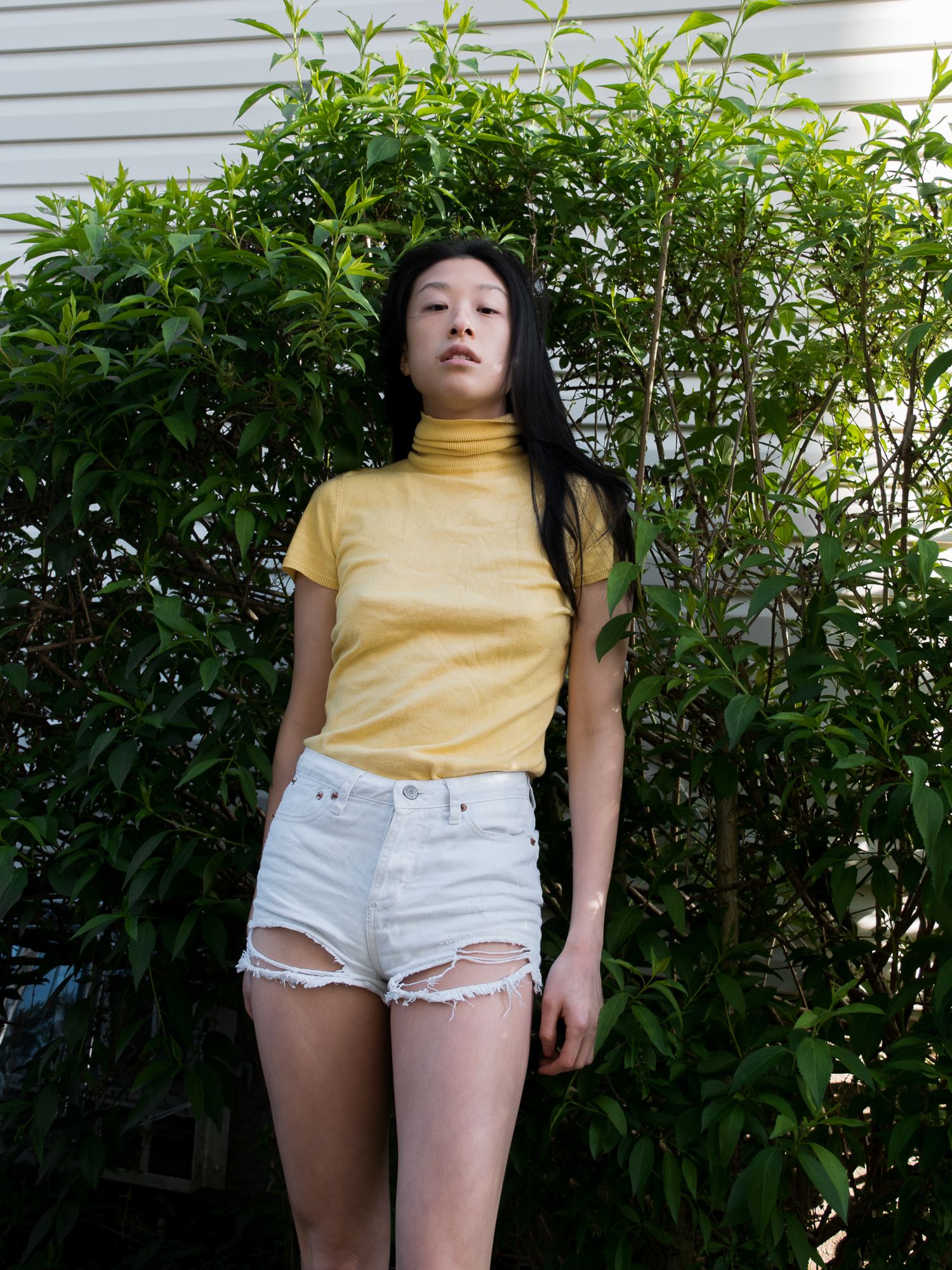 Close-up of female blogger in Yellow short-sleeved turtleneck and distressed white shorts against green leafy background