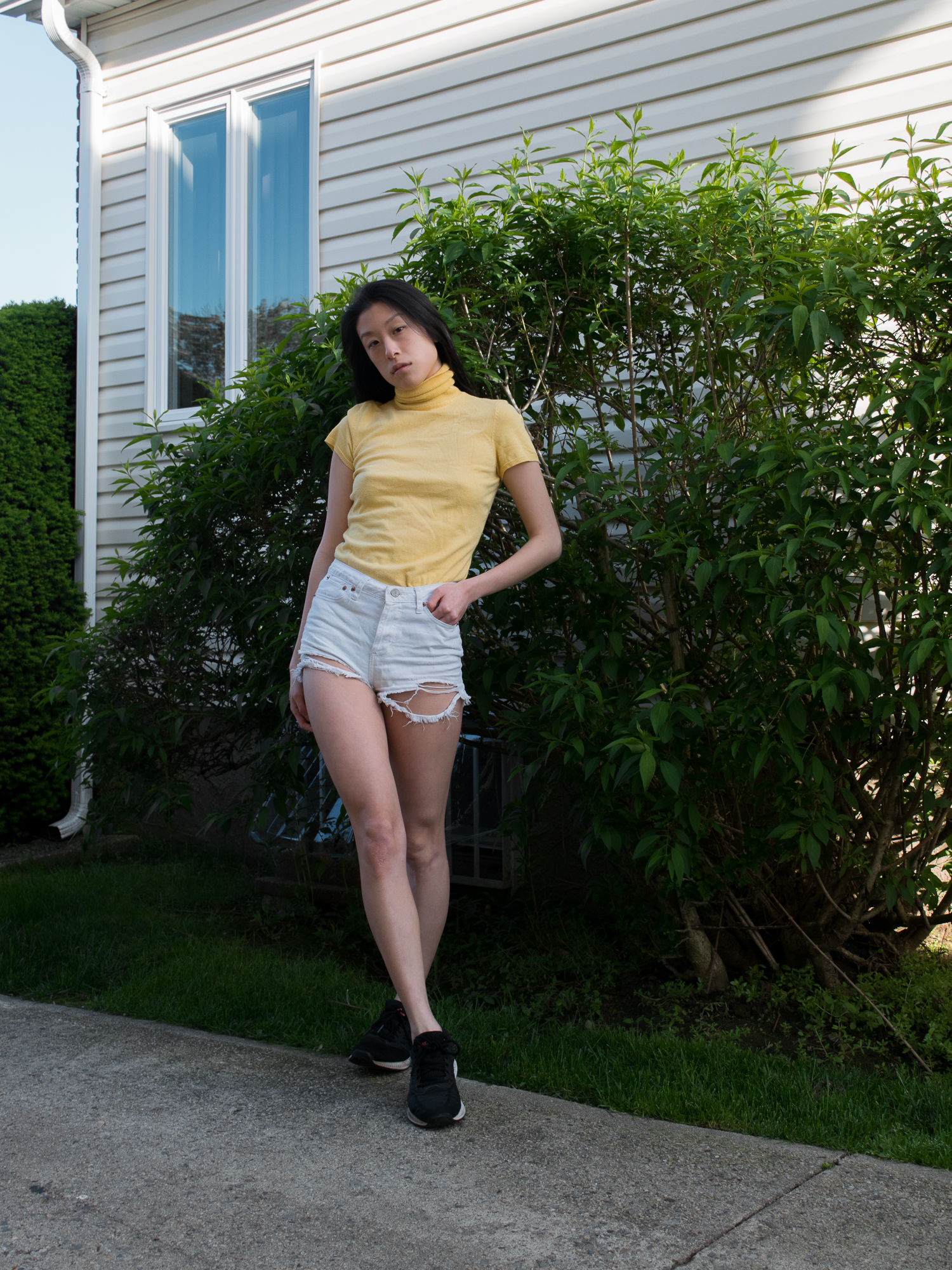 Female wearing yellow turtleneck shirt, white denim shorts, and black sneakers against green bushes