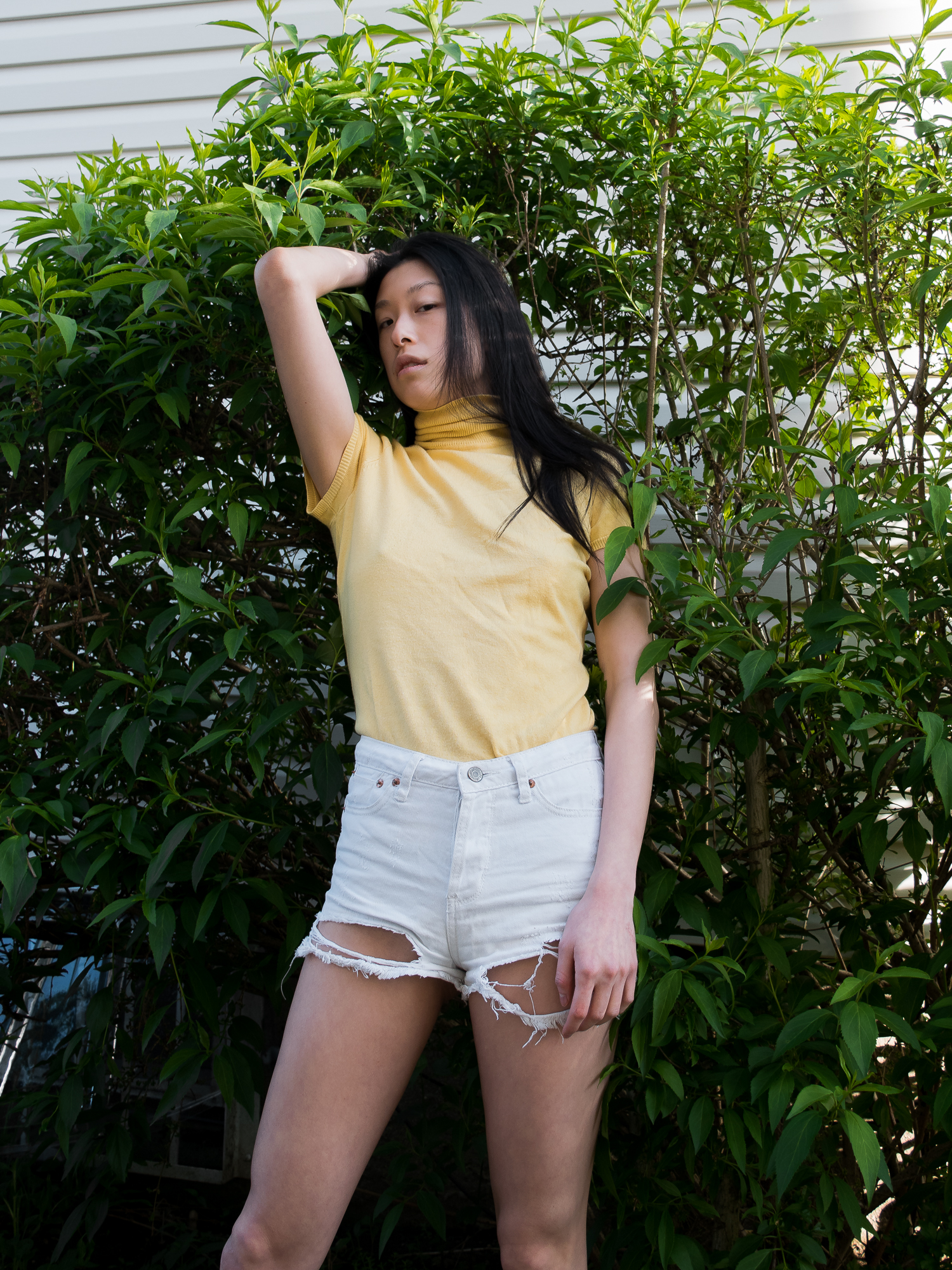 Cute summer outfit close-up, yellow top, white shorts