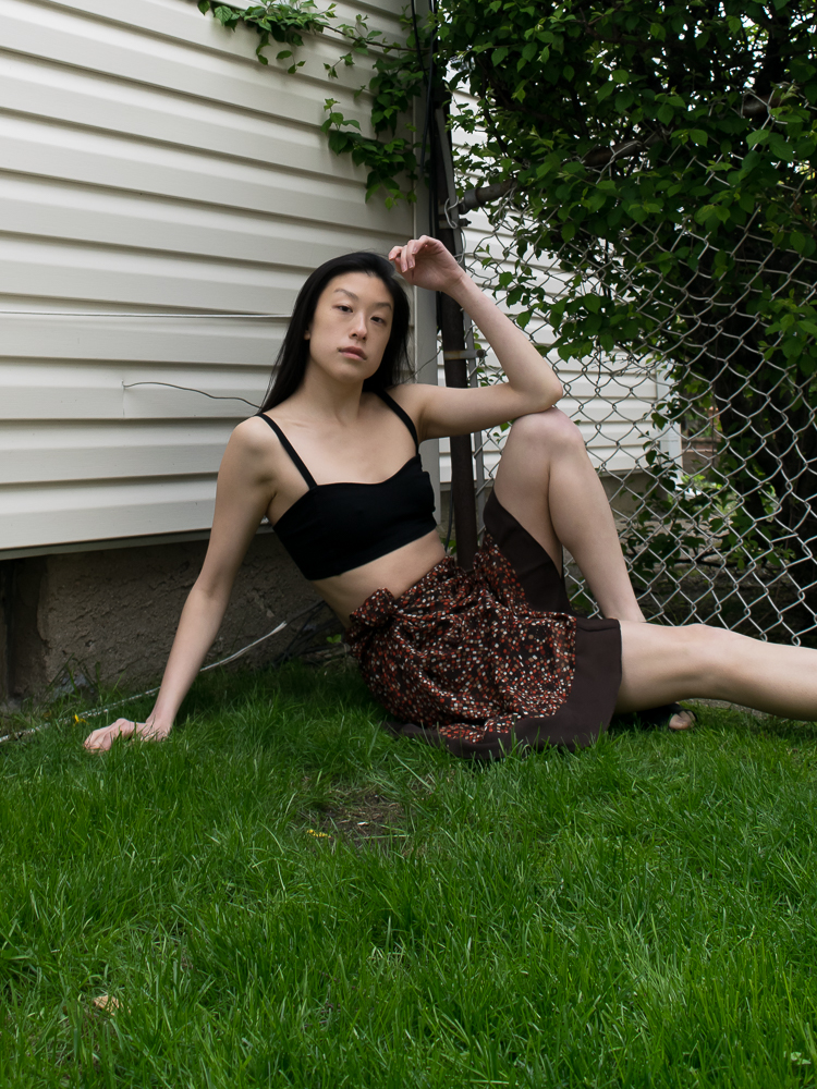 Girl wearing summer outfit with brown polkadot skirt black crop sitting on grass