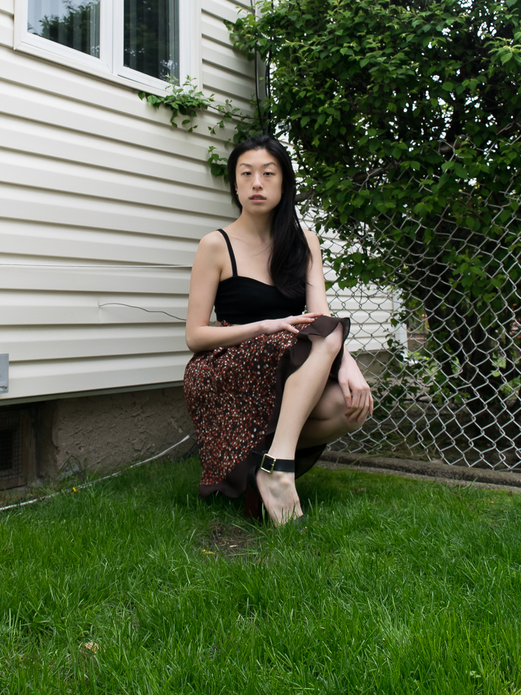 east asian female style blogger in a half-kneel wearing brown skirt, black crop top, on grass