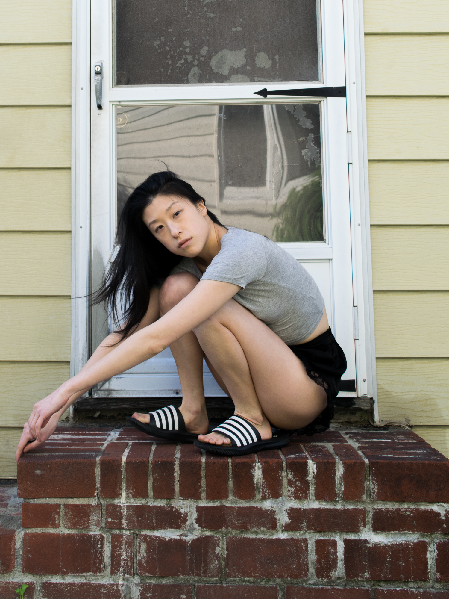 Female, east asian blogger in grey cropped t-shirt, lacy black shorts, black and white striped sandals, posing on brick stoop