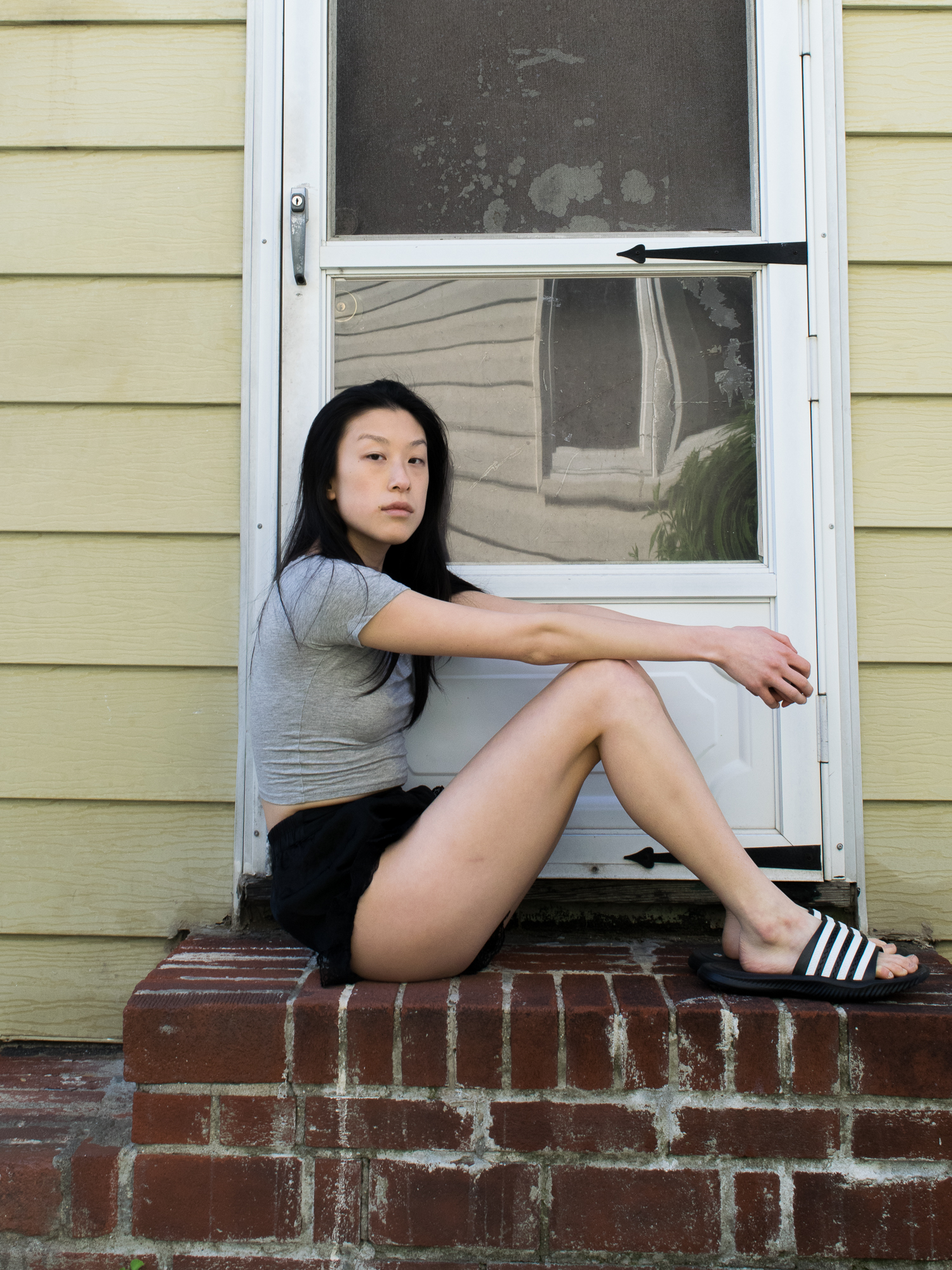 Female, east asian blogger in grey cropped t-shirt, lacy black shorts, black and white striped sandals, sitting on brick stoop