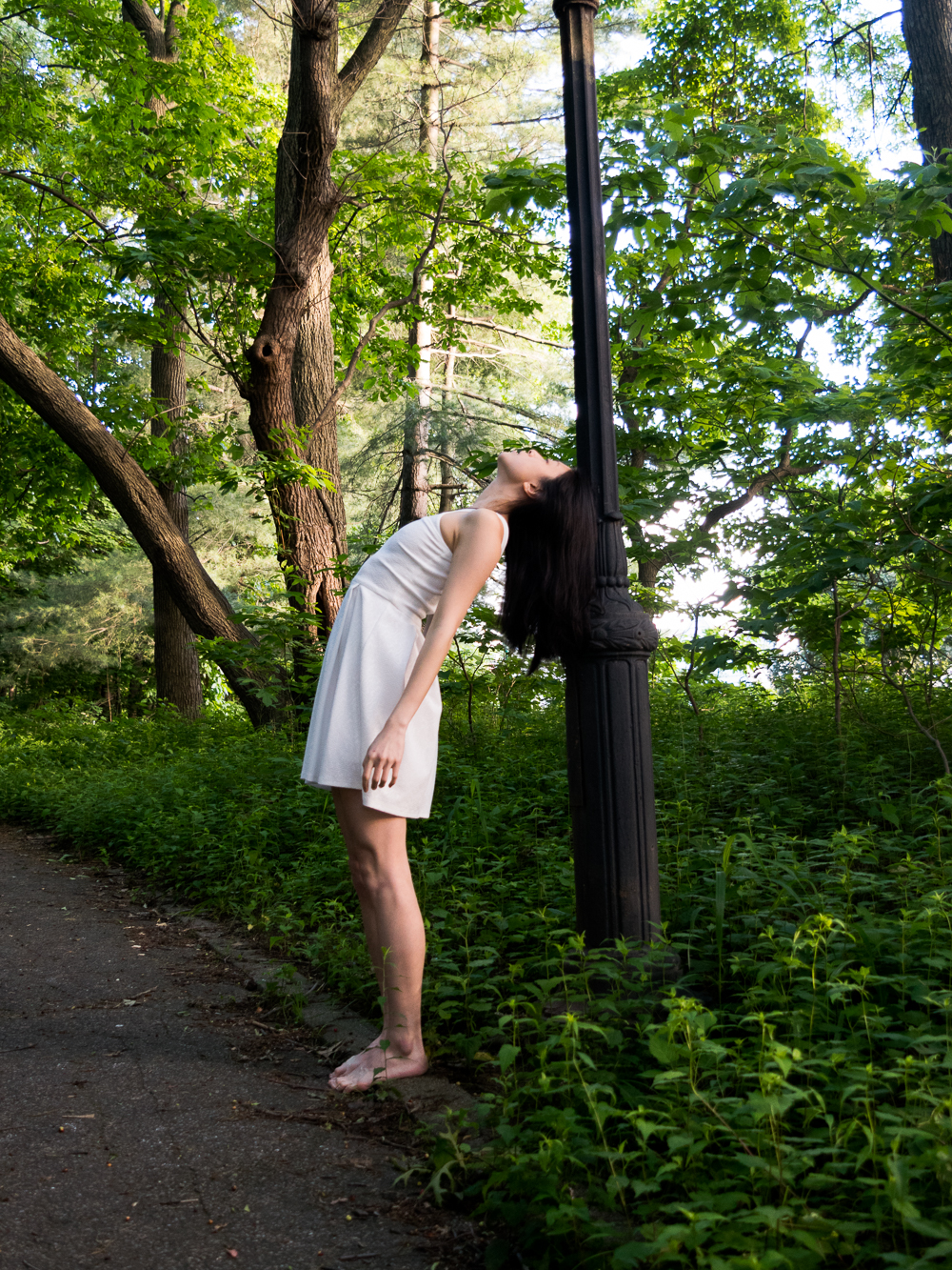 Gi Shieh wearing thrifted white dress, leaning against lamp post, standing in park