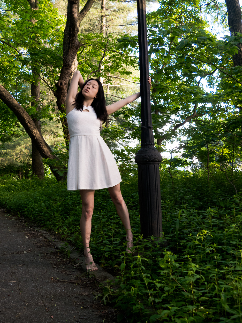 Female east asian style blogger wearing white a-line dress holding on to lamp post in park