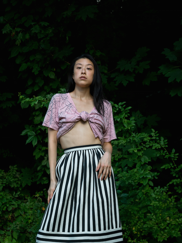 Female east asian style blogger wearing graphic pink tee with striped white and black skirt