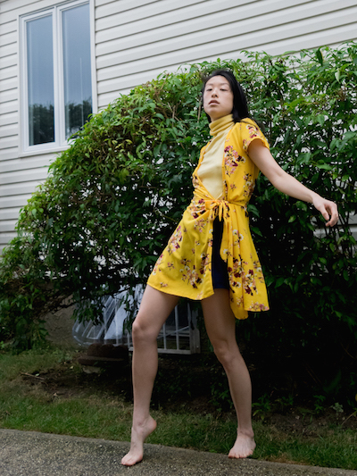 Female east asian style blogger wearing yellow wrap dress, yellow turtleneck top, and navy shorts