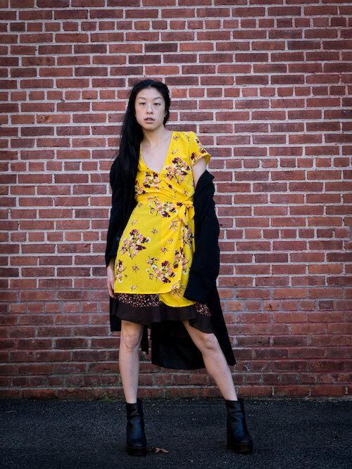 Gi Shieh wearing yellow floral wrap dress, brown polka dot skirt, black trench, black platform boots