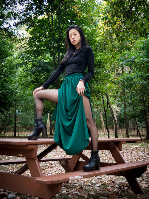 Sustainable style blogger wearing black dress, green skirt, black boots, fishnet tights