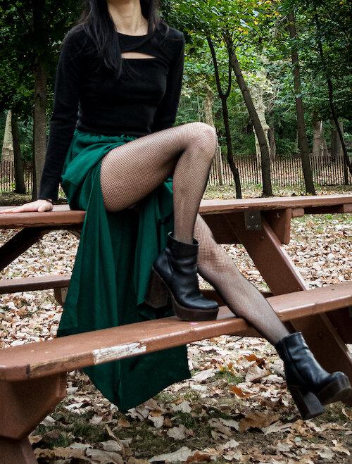Detail shot of green slit skirt, fishnet tights, black platform boots