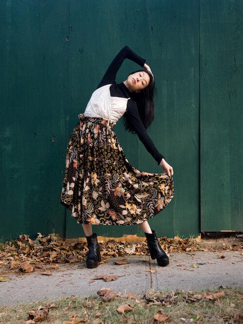 Black turtleneck, silver gold dress, floral skirt, black shoes