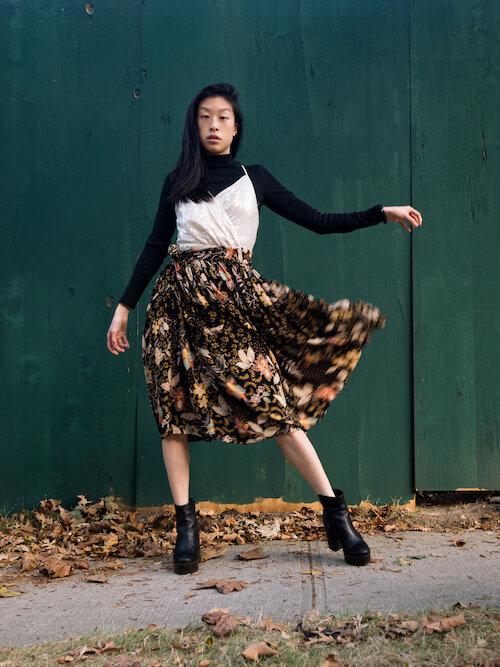 Black turtleneck, floral skirt, black platform boots, white dress