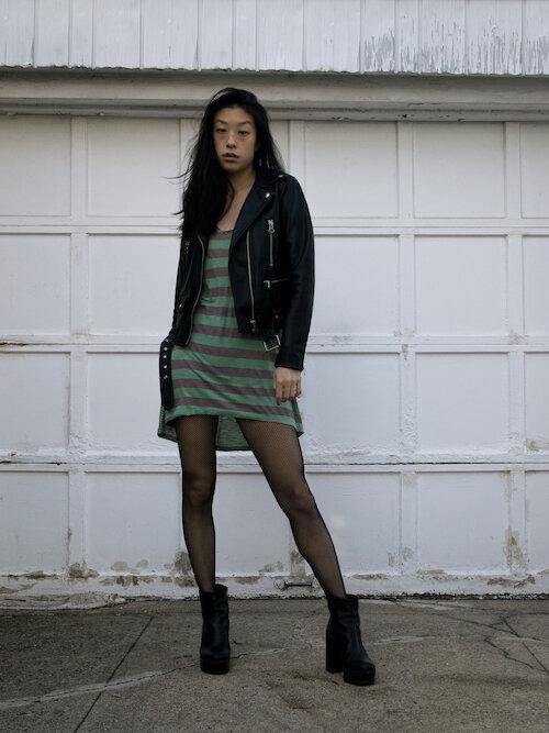 leather jacket, green striped dress, fishnet tights, platform bootss