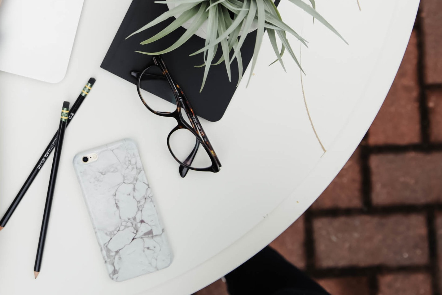 Top Lifestyle Apps for Focus and Productivity | tawnimarie.com | Photo by Corinne Kutz on Unsplash | iphone, glasses, desk, white desk, pencils on desk, iphone on desk, plant on desk