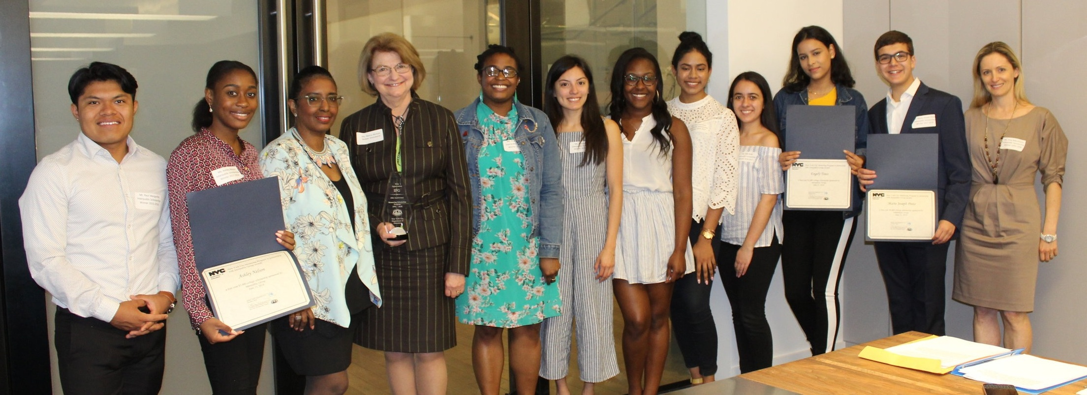 Scholarship winners from 1993 to 2018 present Carolyn Harding and Nancy Rabstejnek Nichols of Interpublic (second and third from left) with a Flame Award in appreciation of the IPG Mentoring Scholarship Program's 25th anniversary.