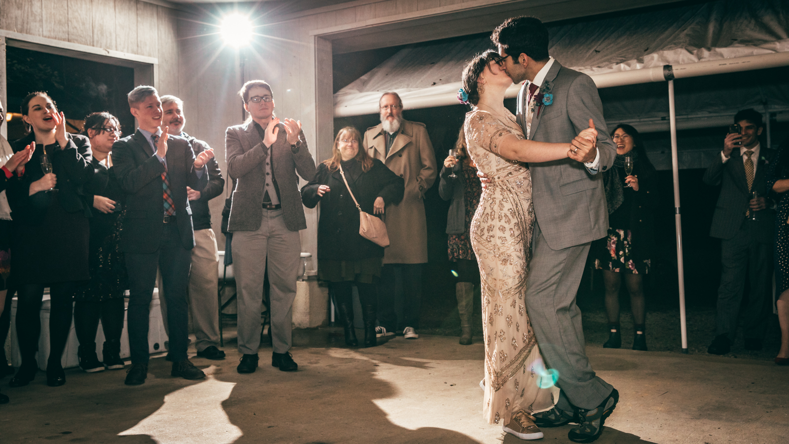 Bride and Groom share a kiss during their first dance at an outdoor wedding reception