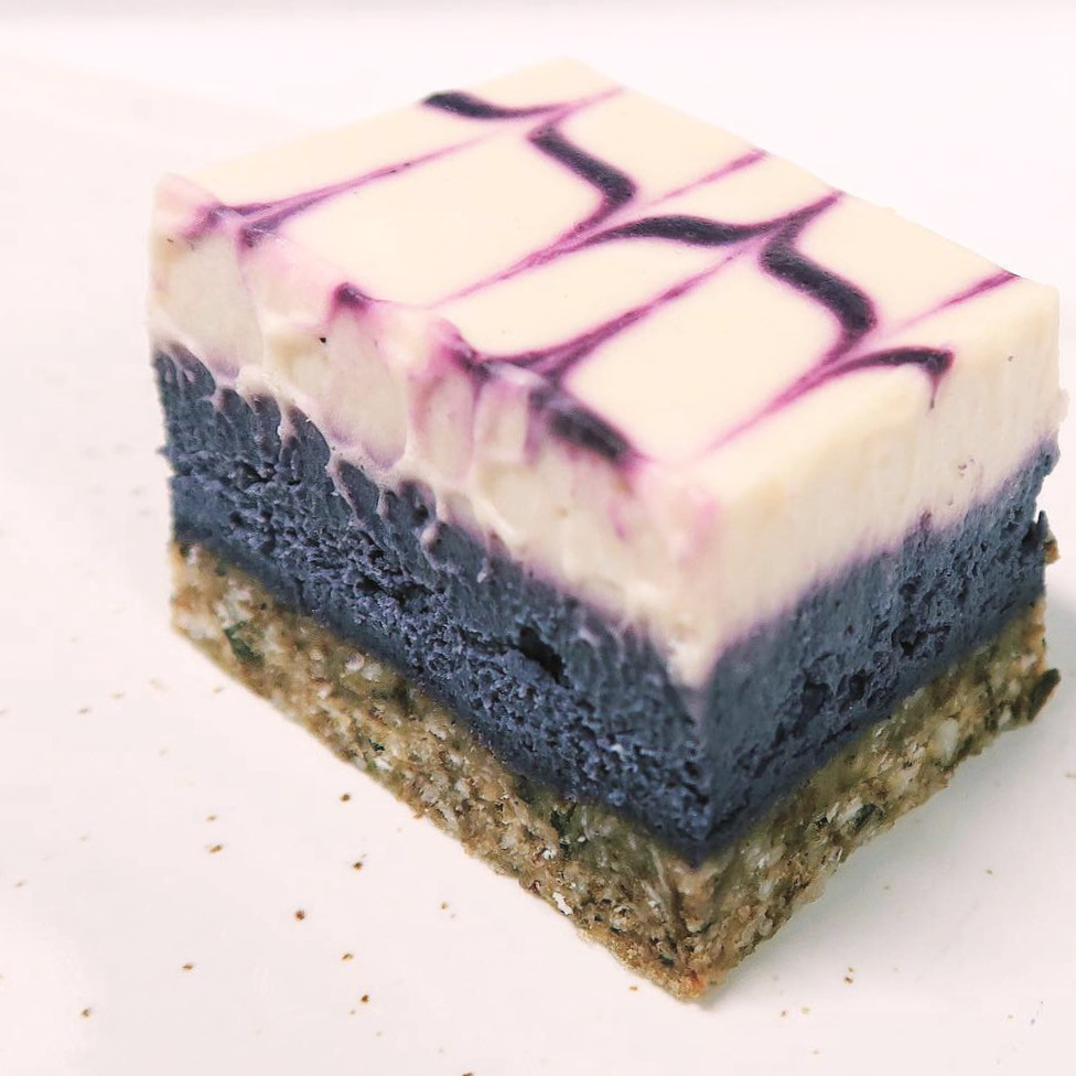 BLUEBERRY LEMON BITE Ingredients:  Coconut cream , cashews, almonds,  coconut oil, dates, raisins, desiccated coconut flakes, blueberries, lemon juice, agave, cocoa butter, psyllium, agar-agar, salt.