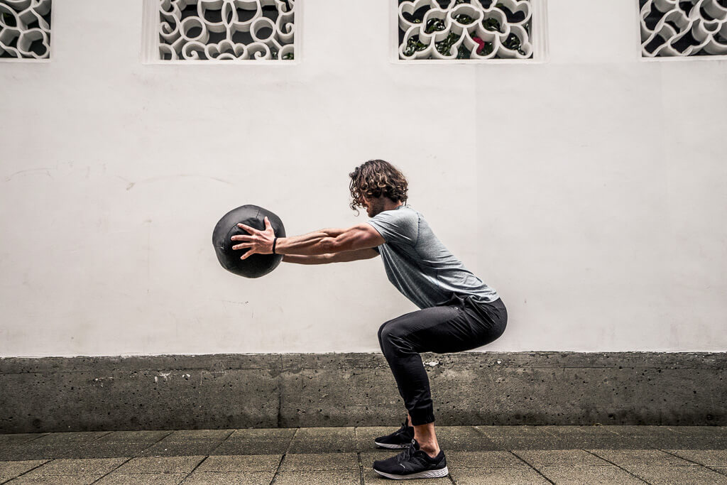 Medicine ball front squat form. Hold the ball directly out from your chest and squat, do not let your knees go past your toes. Try to sit back in a 90 degree angle, as if an invisible chair is there.