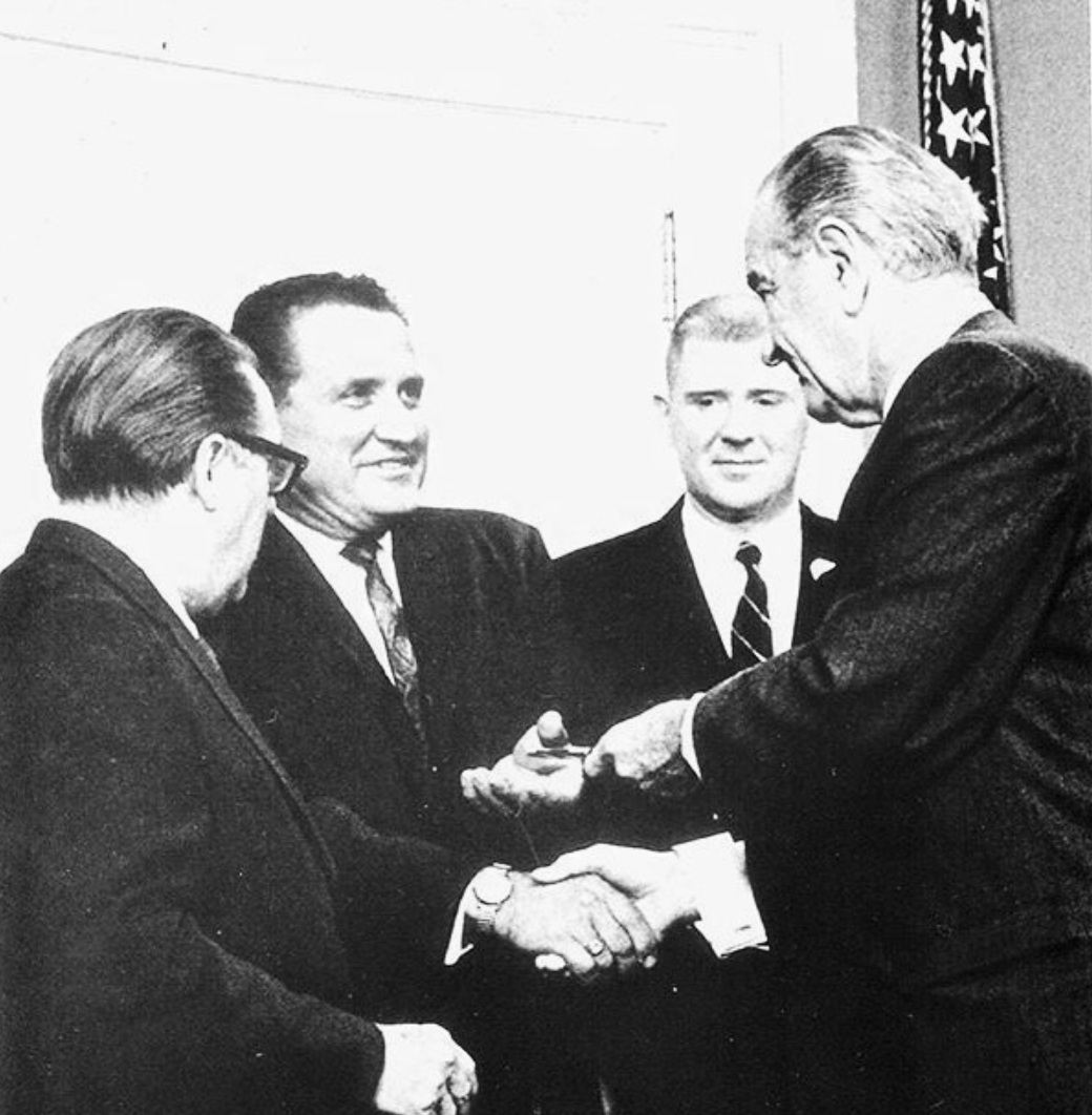 U.S. President Lyndon B. Johnson hands Washington State Insurance Commissioner Karl Herrmann the pen used to sign a pro-consumer law advocated by Herrmann. Washington Senator Warren Magnuson stands beside Herrmann on the left.