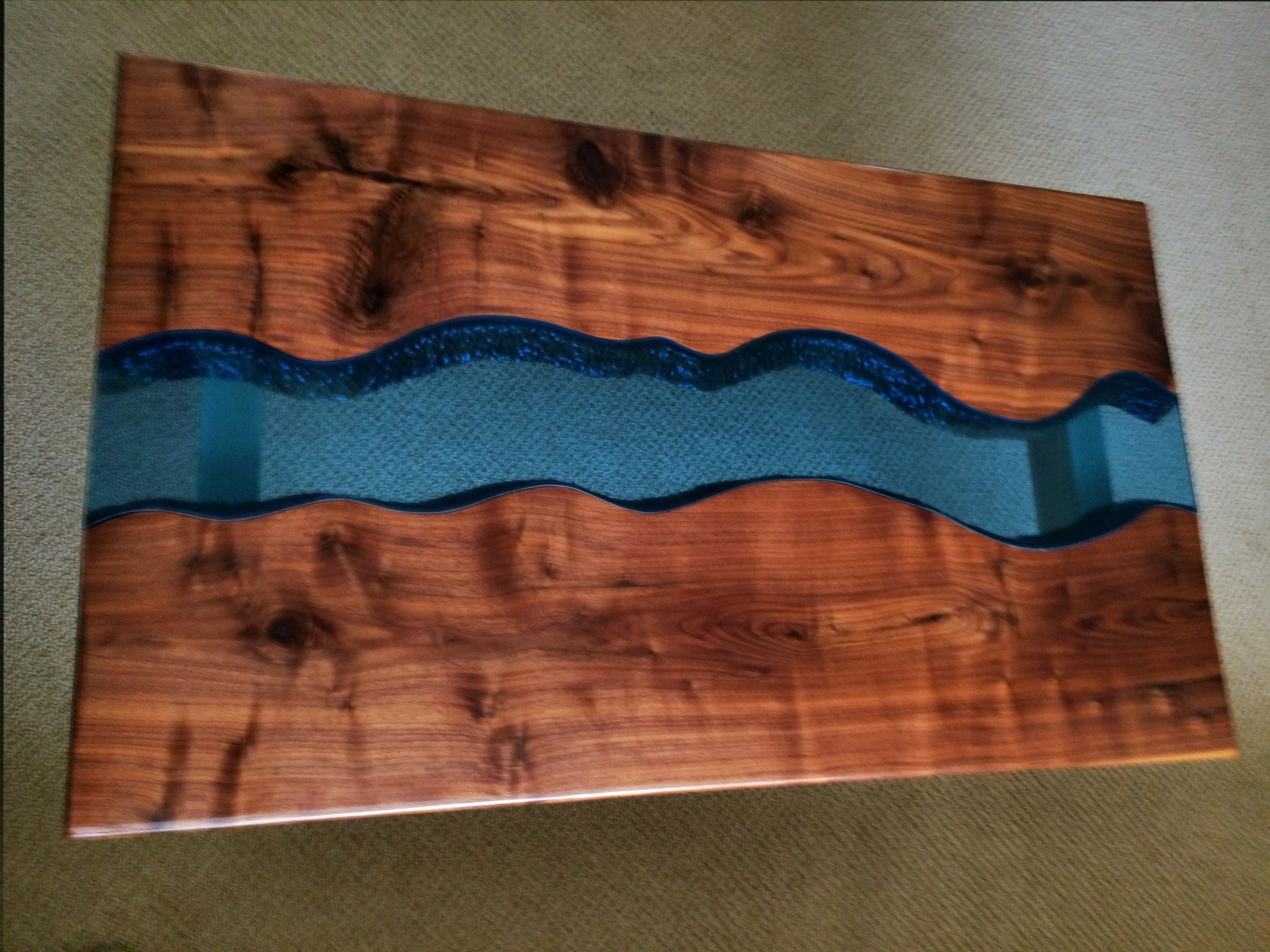 "River Coffee Table - Here is a coffee table I made out of black walnut for the top, maple for the legs, and blue glass for the water. I could not find a source for ""live-edge"" walnut, so I carved out the channel for the river by hand and machine tools."