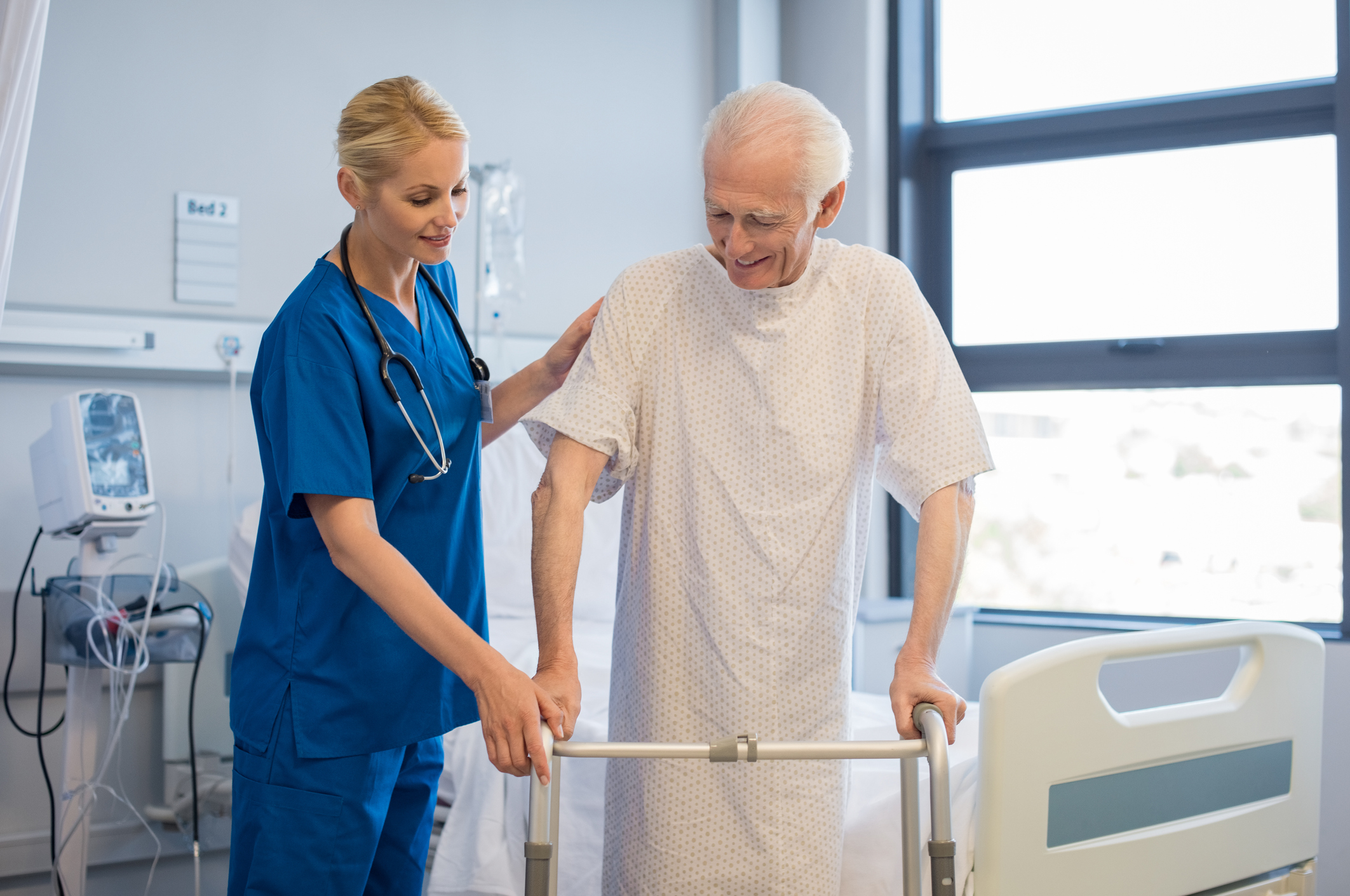 Nurse helping senior man in facility with walker