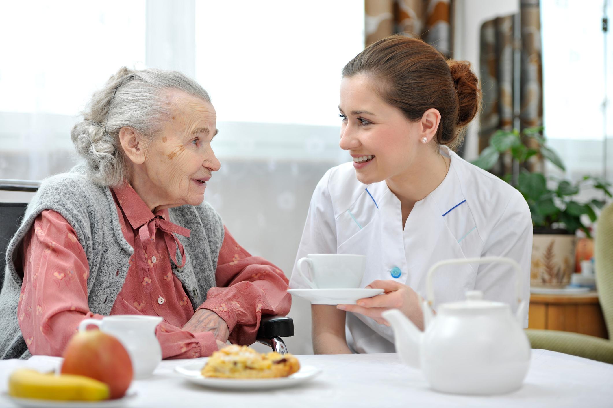 Nurse giving senior woman a cup of tea