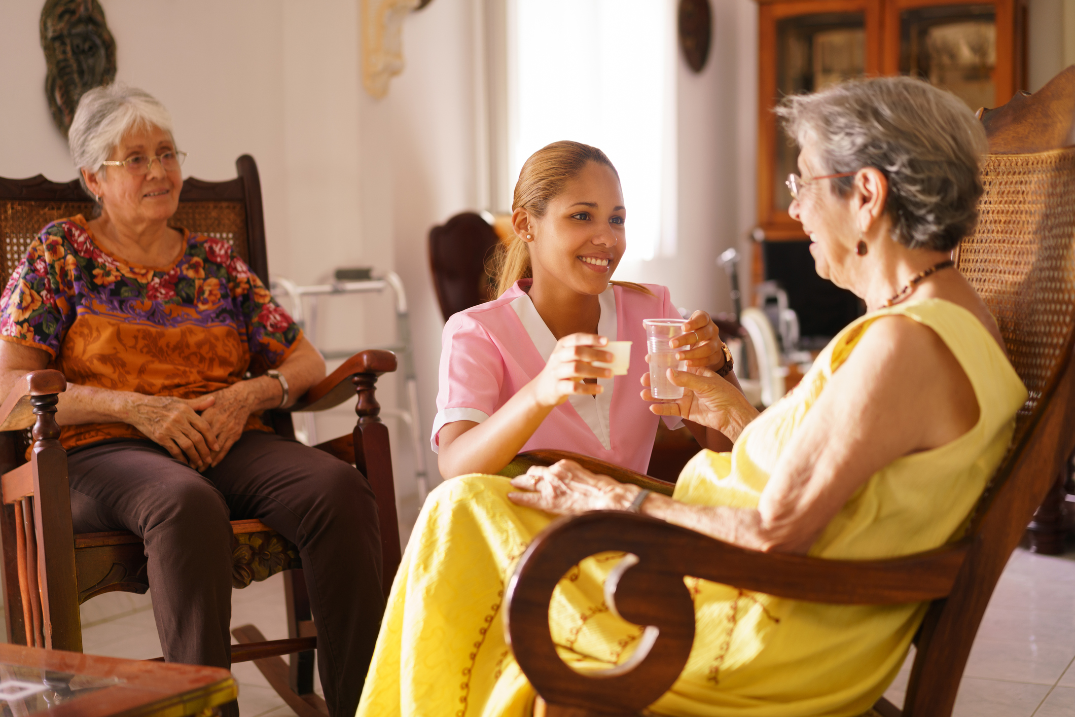 Certified nursing assistant giving woman in rocking chair pills and water cup while woman in rocking chair looks on