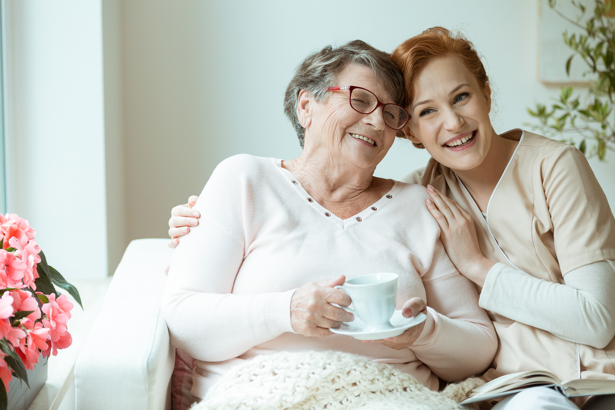 Nursing assistant embracing senior woman smiling and holding a tea cup