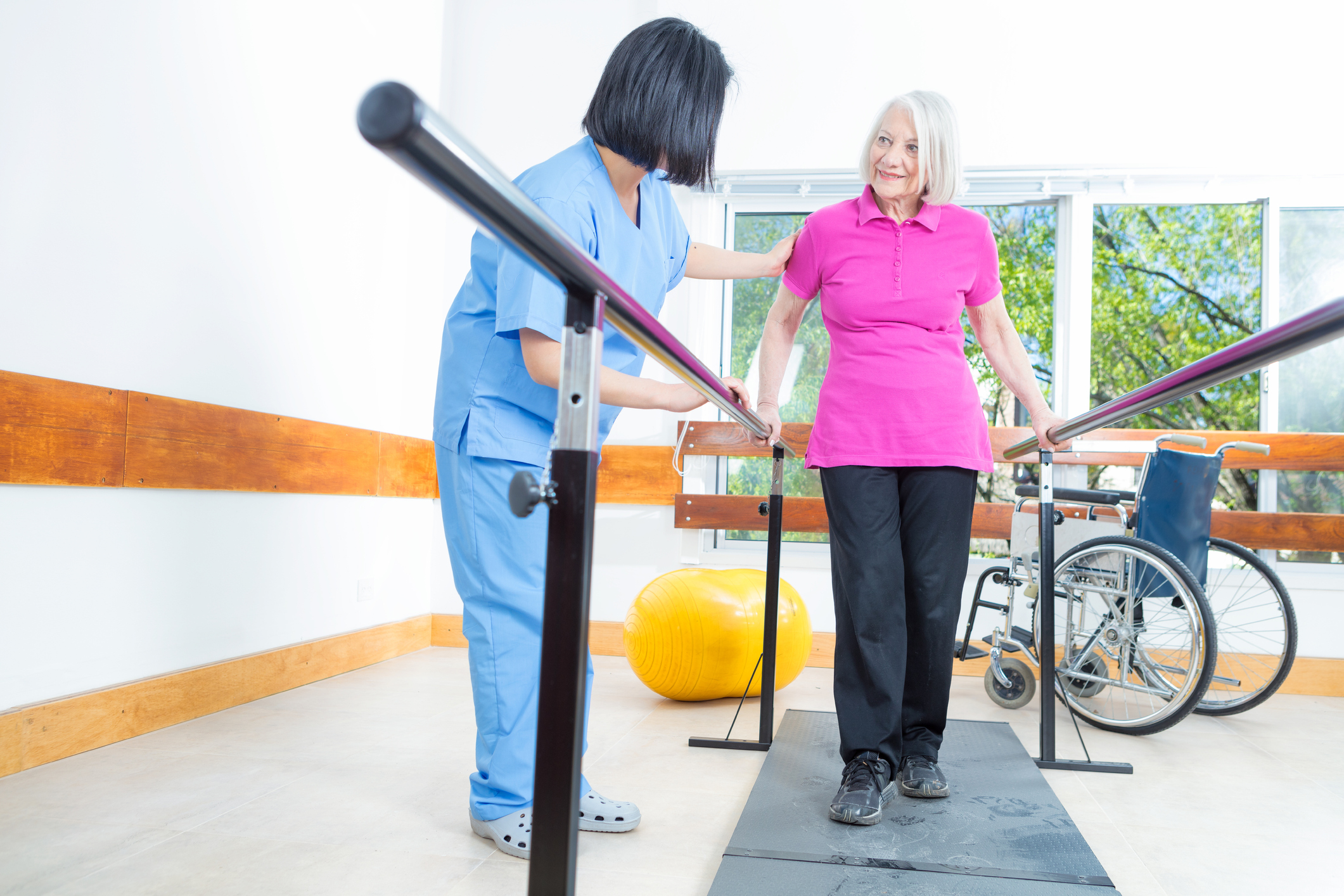 Therapist helps older woman walk using parallel bars