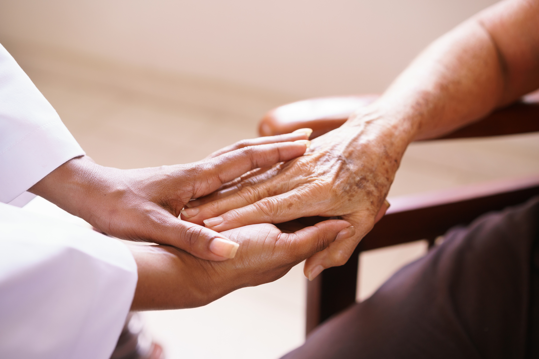 Younger nurse hands hold older person's hand